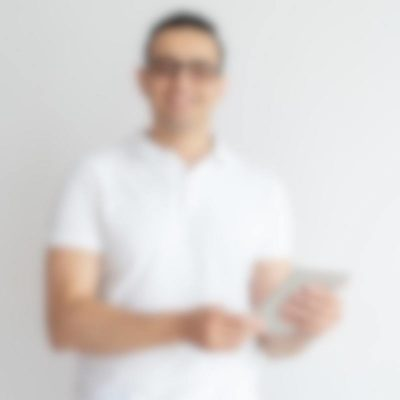 Smiling young man using tablet computer. Attractive guy wearing glasses, browsing on tablet and looking at camera. Technology concept. Isolated front view on white background.